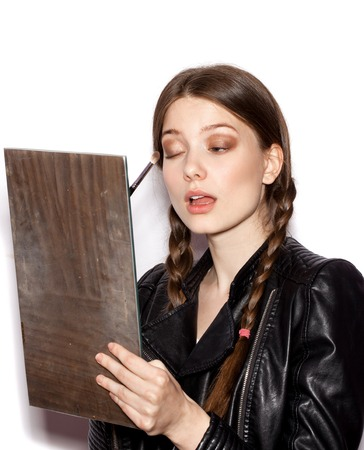 cheekbones: Beauty woman applying makeup. Beautiful girl looking in the mirror and applying cosmetic with a big brush. Girl gets blush on the cheekbones. White background not isolated