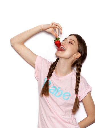 teenage girl: Young cheerful girl having fun and enjoying strawberry. Smiling Woman with bright makeup and hairstyle with pigtails. White background not isolated