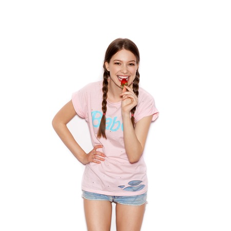 woman diet: Young cheerful girl having fun and enjoying strawberry. Smiling Woman with bright makeup and hairstyle with pigtails. White background not isolated