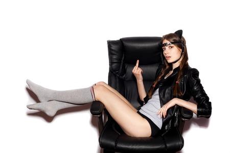 猫耳の若い女性は黒のオフィス椅子を中指の上に座る。ファッションの流行に敏感な女の子。 白い背景に、孤立していません。
