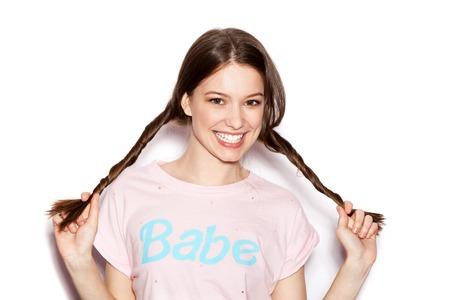 jeune fille: Jeune fille gaie ayant amusant. Sourire femme avec maquillage lumineux et la coiffure avec des tresses. Fond blanc pas isol�