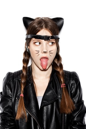 pretty young girl: Funny girl represents as small cat.  Woman  with bright makeup hairstyle of girl with leather cat ears having fun. On white background not isolated Stock Photo