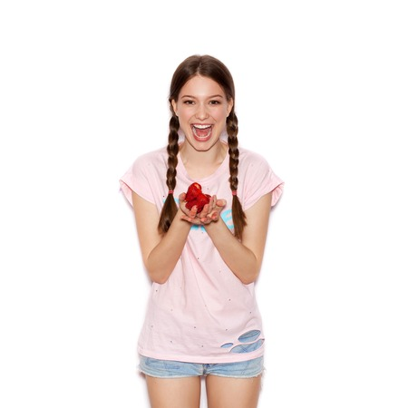 face paint: Young cheerful girl having fun and  holding ripe strawberry. Smiling Woman with bright makeup and hairstyle with pigtails. White background not isolated Stock Photo