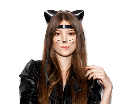Funny girl represents as small cat.  Woman  with bright makeup hairstyle of girl with leather cat ears having fun. On white background not isolated Stock Photo