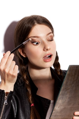 brunette girl: Beauty woman applying makeup. Closeup of girl looking in the mirror and applying cosmetic with big brush. White background not isolated