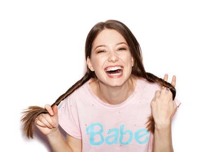 Young cheerful girl having fun. Smiling Woman with bright makeup and hairstyle with pigtails. White background not isolated