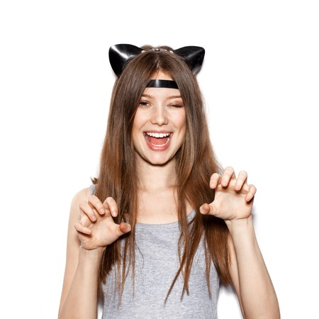 casual fashion: Funny girl represents as small cat.  Woman  with bright makeup hairstyle of girl with leather cat ears having fun. On white background not isolated Stock Photo