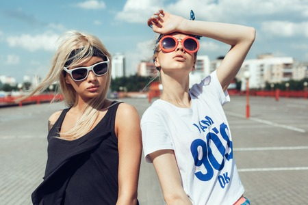 Two beautiful happy girls in sunglasses looking into the distance on the urban background. Young active people. Outdoors Stockfoto