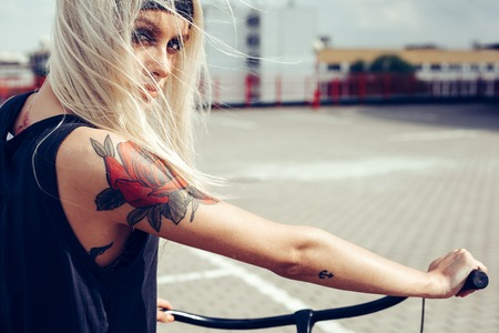 Pretty blonde woman with bike in city. Soft sunny color outdoors portrait Reklamní fotografie