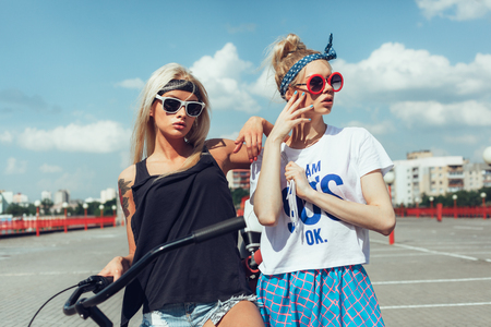 swag: Outdoor fashion portrait of attractive young women with bicycle and roller skates. Two teen swag girls