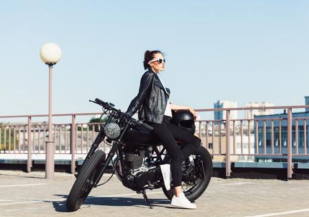 Biker girl in leather jacket sitting on vintage custom motorcycle. Outdoor lifestyle portrait Stock Photo