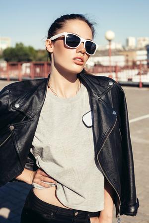 femme brune sexy: Glamorous jeune femme en veste de cuir noir. Mode de vie portrait en plein air