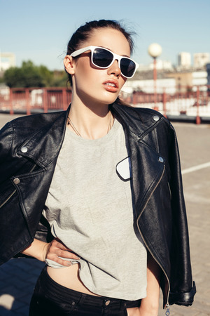 girl posing: Glamorous young woman in black leather jacket. Outdoor lifestyle portrait