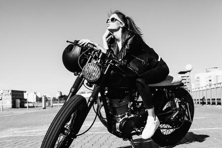 casco de moto: Muchacha del motorista sienta en la motocicleta de encargo de la vendimia. Negro blanco al aire libre retrato estilo de vida Foto de archivo