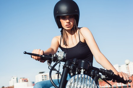 a helmet: Biker girl in helmet sitting on vintage custom motorcycle. Outdoor lifestyle portrait