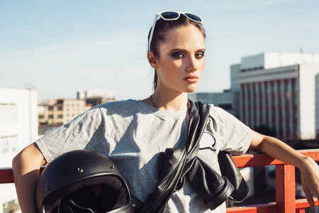 fashion model: Young female biker holding a motorcycle helmet. Outdoor lifestyle portrait