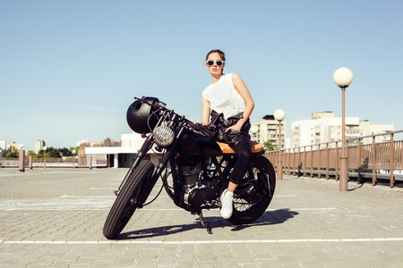 Biker girl in leather jacket sitting on vintage custom motorcycle. Outdoor lifestyle portrait Stockfoto