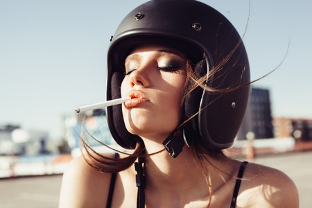 black girl smoking: Close-up of Beautiful smoking girl in helmet. Outdoor lifestyle portrait