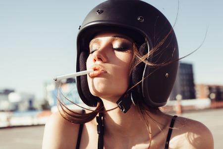 smoking girl: Close-up of Beautiful smoking girl in helmet. Outdoor lifestyle portrait