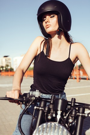 casual fashion: Biker girl sitting on vintage custom motorcycle. Outdoor lifestyle portrait