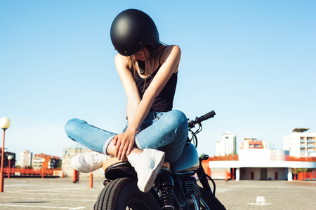 biker girl: Biker girl sitting on vintage custom motorcycle. Outdoor lifestyle portrait