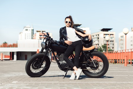 Biker girl in leather jacket sitting on vintage custom motorcycle. Outdoor lifestyle portrait Reklamní fotografie