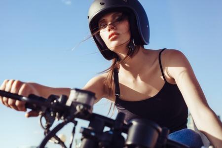 trend: Biker girl in helmet sitting on vintage custom motorcycle. Outdoor lifestyle portrait