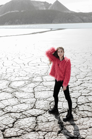 cracked: Young woman walking on dry land. Outdoors lifestyle portrait