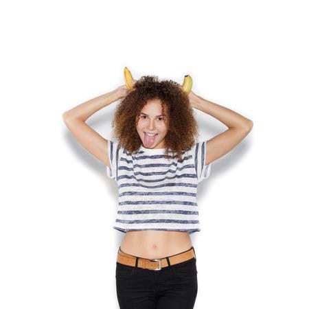 banane: Jolie jeune fille faisant plaisir avec la banane. Femme avec coiffure afro tenant la banane comme des cornes sur fond blanc pas isol�s Banque d'images
