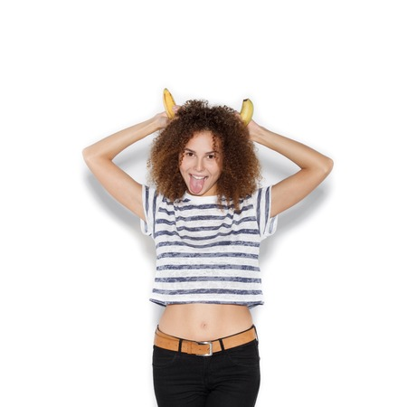 banana: Young pretty girl making fun with banana. Woman with afro hairstyle holding banana as horns over white background not isolated