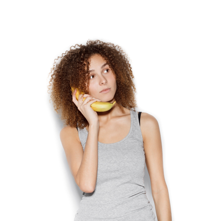 comiendo frutas: Young pretty girl making fun with banana. Woman holding a banana as a telephone over a white background not isolated