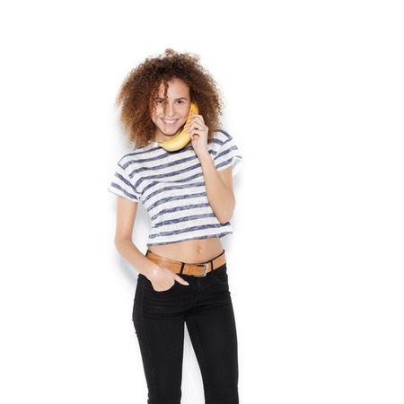 white people: Young pretty girl making fun with banana. Woman holding a banana as a telephone over a white background not isolated