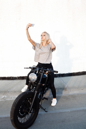 sexy pictures: Sexy fashion female biker girl taking selfie with vintage custom motorbike. . Young Blonde woman  with mobile smartphone. Outdoors lifestyle portrait