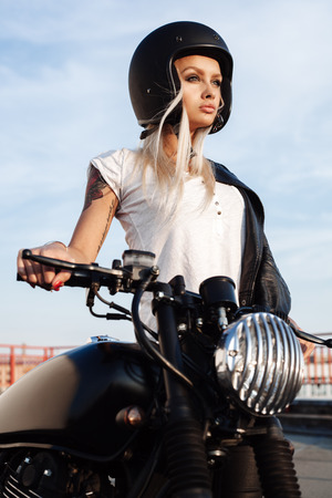 Sexy fashion female biker girl in open face helmet. Woman with vintage custom black motorbike. Outdoor lifestyle portrait