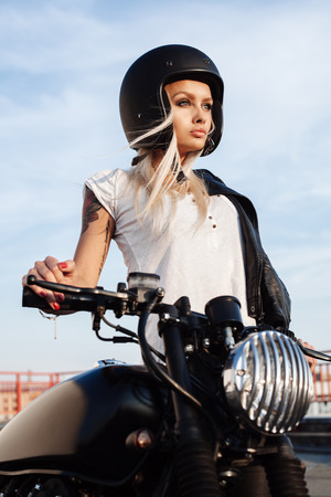 Female biker girl in black open face helmet. Woman with vintage custom motorbike. Outdoor lifestyle portrait