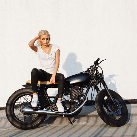 biker: Fashion female biker girl. Young Blonde woman in leather jacket sitting on vintage custom motorbike. Outdoors lifestyle portrait Stock Photo