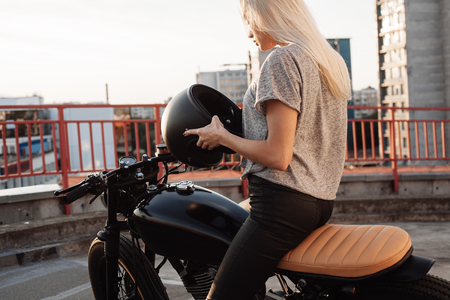 fashionable girl: Fashion female biker girl. Young Blonde woman in leather jacket sitting on vintage custom motorbike. Outdoors lifestyle portrait Stock Photo