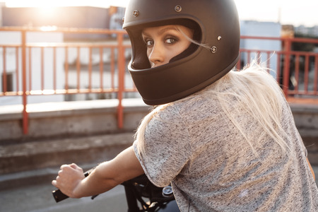 Sexy fashion female biker girl with black full face motorcycle helmet. Young Blonde woman  sitting on vintage custom motorbike. Outdoors lifestyle portrait