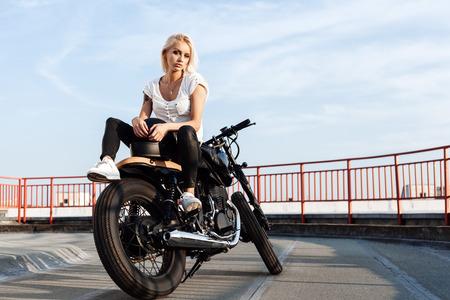 casco moto: Retrato del modelo motorista femenino sentado en la motocicleta de encargo de la vendimia. Al aire libre retrato estilo de vida