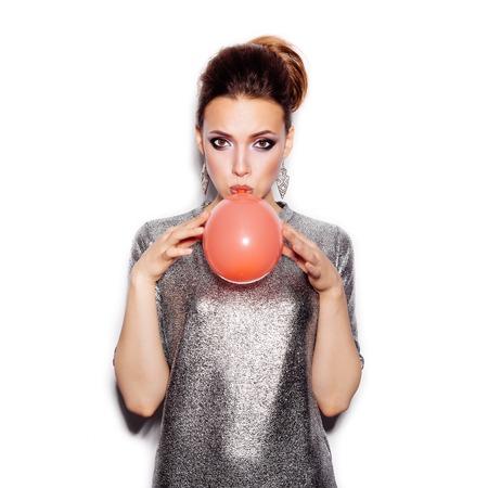 globo: Beauty Girl Fashion soplando un globo rojo. Retrato de la mujer. Corte de pelo y maquillaje con estilo. Estilo Vogue. En el fondo blanco no aislados