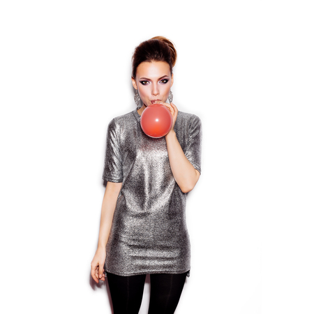 Fashion Beauty Girl blowing a red balloon. Gorgeous Woman Portrait. Stylish Haircut and Makeup. Vogue Style. On White background no isolated Stockfoto
