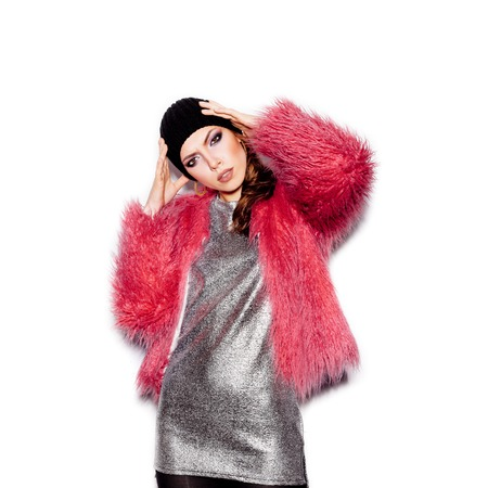 pink fur: Fashion Beauty Swag Girl wearing silver dress, pink fur coat, black beanie hat. Stylish Haircut and Makeup. Gorgeous young Woman posing on white background no isolated