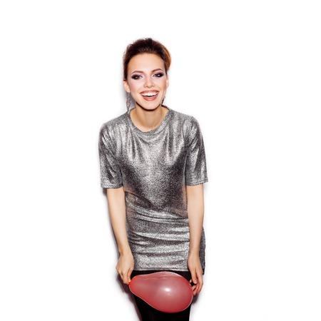 jovencitas: Joven mujer feliz con vestido plata y que sostiene el globo de color rosa sobre fondo blanco no aislados