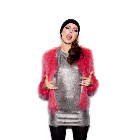 beanie: Fashion Beauty Swag Girl wearing silver dress, pink fur coat, black beanie hat. Stylish Haircut and Makeup. Gorgeous young Woman posing on white background no isolated