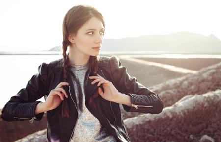 modelos posando: Mujer atractiva joven con trenzas vestida con un vestido de plata y chaqueta de cuero. Moda joven disfrutando de unas vistas impresionantes de la ladera. Aire libre retrato estilo de vida Foto de archivo