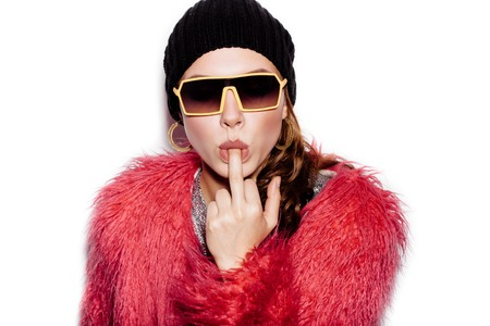 beanie: Fashion Beauty Swag Girl wearing silver dress, pink fur coat, black beanie hat. Stylish Haircut and Makeup. Young sexy Woman sucking middle finger on white background no isolated