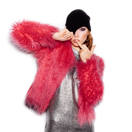 middle finger: Fashion Beauty Swag Girl wearing silver dress, pink fur coat, black beanie hat. Stylish Haircut and Makeup. Gorgeous young Woman kissing middle finger on white background no isolated