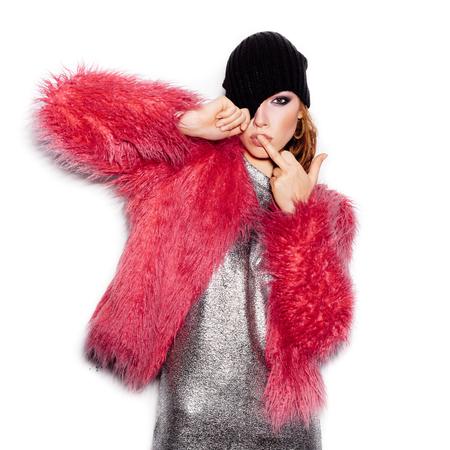 bacio: Moda bellezza Swag ragazza vestito d'argento da portare, cappotto di pelliccia rosa, cappello nero del beanie. Taglio di capelli alla moda e il trucco. Splendida giovane donna che bacia dito medio su sfondo bianco non isolato