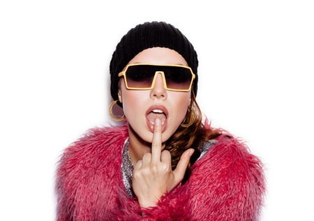 finger on lips: Fashion Beauty Swag Girl wearing sunglasses, pink fur coat, black beanie hat. Stylish Haircut and Makeup. Young Woman licking middle finger on white background no isolated