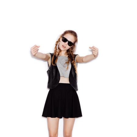 the finger: Chica adolescente en gafas de sol mostrando el dedo medio. Mujer joven que se divierte. No aislado sobre fondo blanco